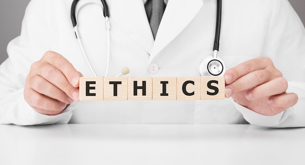 Doctor holds wooden cubes in his hands with text ethics