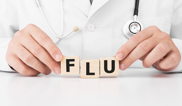 Doctor holds wooden cubes in his hands with text flu