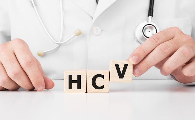 Doctor holds wooden cubes in his hands with text hcv