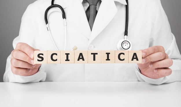 Doctor holds wooden cubes in his hands with text sciatica