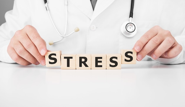 Doctor holds wooden cubes in his hands with text stress