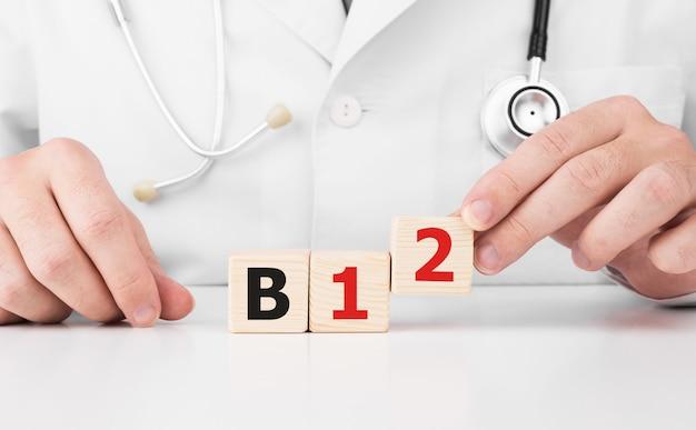 医者はテキストb12で彼の手に木製の立方体を持っています
