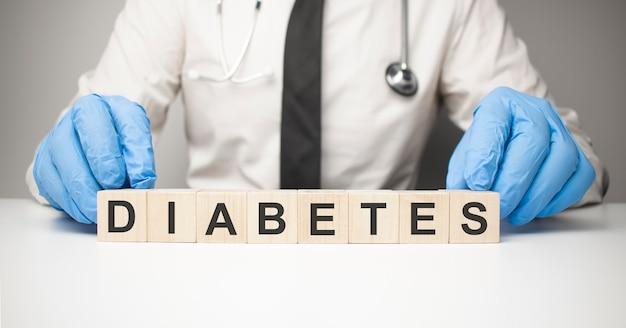 Доктор держит в руках деревянные кубики с текстовым диабетом