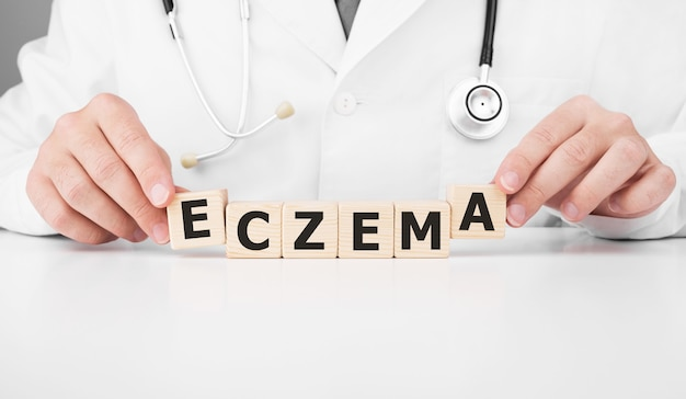 医者はテキストeczemaで彼の手に木製の立方体を持っています