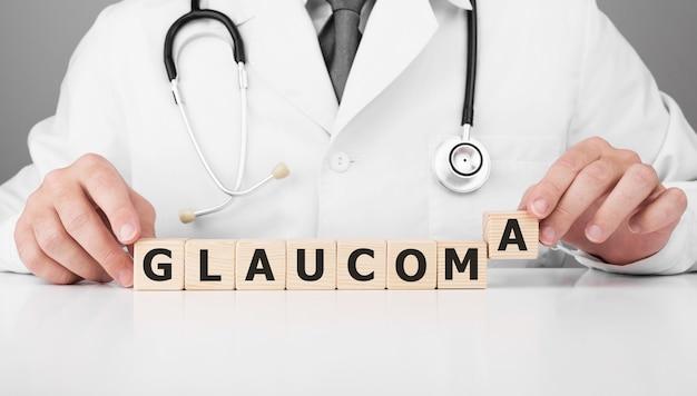 의사는 glaucoma 텍스트와 함께 그의 손에 나무 큐브를 보유