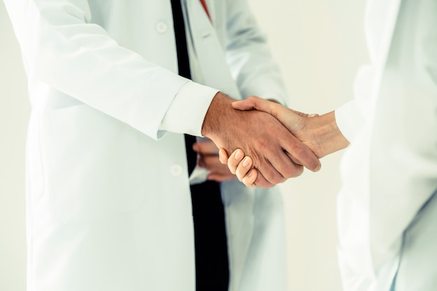 Doctor at hospital shakes hand with another doctor
