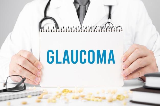 Доктор в халате держит блокнот с текстом глаукома, медицинская концепция