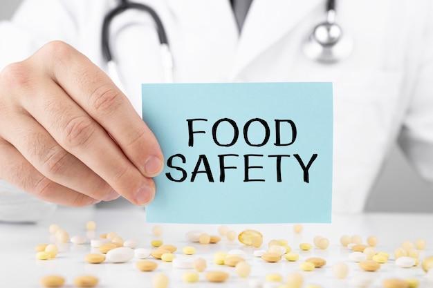 Врач в халате держит наклейку с надписью безопасность пищи