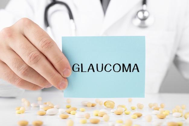 Врач в халате держит наклейку с текстом глаукома
