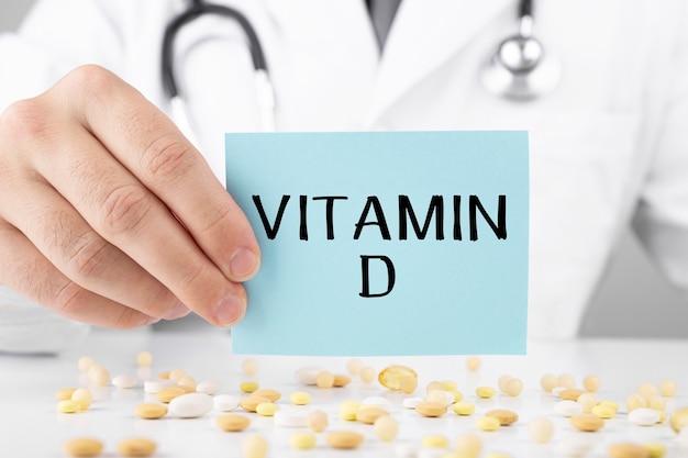 드레싱 가운을 입은 의사가 텍스트 비타민 d 스티커를 들고 있습니다.