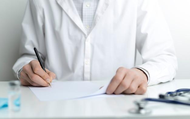 ドレッシングガウンの医者が職場で処方箋を書く