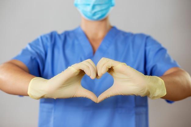 Доктор в маске и перчатках, образующих сердце перед синей рубашкой,
