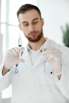 그의 손에 주사기와 백신 보호 장갑이 달린 앰플이있는 의료 가운 의사