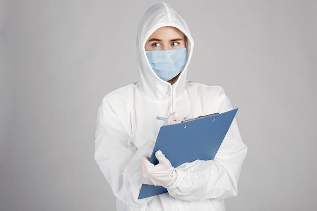 医療用マスクの医者。コロナウイルスのテーマ。白い背景の上に分離されました。防護服を着た女性。