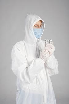 의료 마스크에 의사. 코로나 바이러스 테마. 흰색 배경 위에 격리. 환 약을 가진 여자입니다.