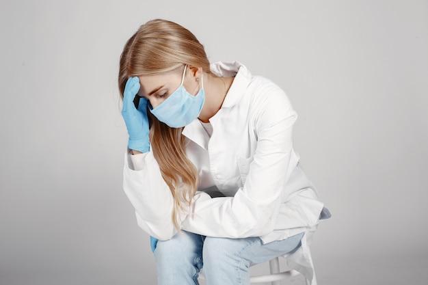 医療用マスクの医者。コロナウイルスのテーマ。白い壁に隔離。医者のために祈ってください。