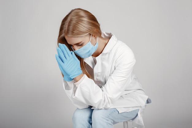 Врач в медицинской маске. тема коронавируса. изолированный над белой стеной. молитесь за врачей.