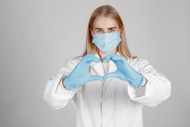 医療用マスクの医者。コロナウイルスのテーマ。白い壁に隔離