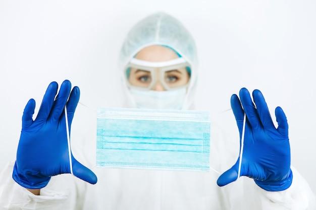 白い壁に医療マスクの医師。コロナウイルスの流行における消毒剤の使用。 covid2019。医師のサポート-家にいて。