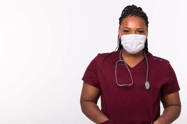 Доктор в медицинской маске над белой стеной с копией пространства