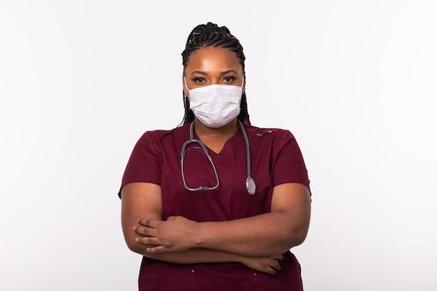 Доктор в медицинской маске над белой стеной