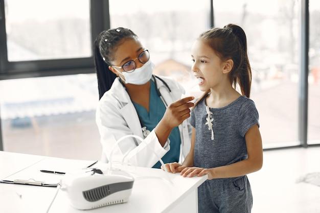 보호 마스크에 의사. 아이가 흡입을합니다. 아프리카 여자.