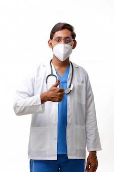 聴診器と白い背景の上に親指を表示して白衣を着た医師。