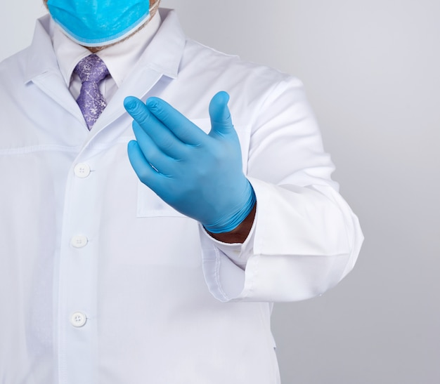 ボタンと青いラテックス手袋の白いコートを着た医者が彼の手を差し出し、招待の概念