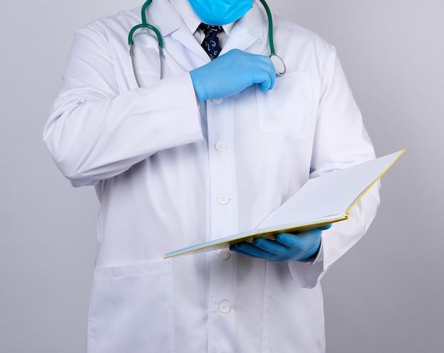 ボタンの付いた白衣を着た医師、青い滅菌手袋を着用、紙の開いたノートを手に持った医師