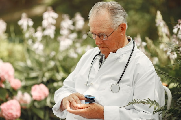 Врач в белой форме. старик сидит в летнем парке. старший со стетоскопом. мужчина измеряет пульс на пальце.