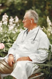 Врач в белой форме. старик сидит в летнем парке. старший со стетоскопом.