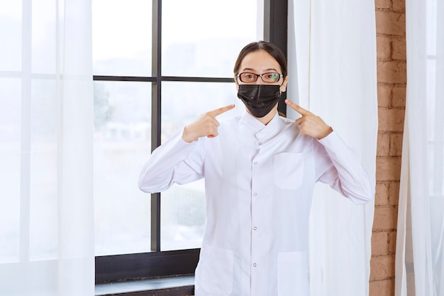 窓際に立ってマスクを指さしている黒いマスクと眼鏡の医者。