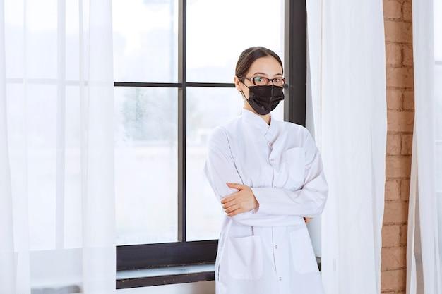 窓際に立っている黒いマスクと眼鏡の医者。