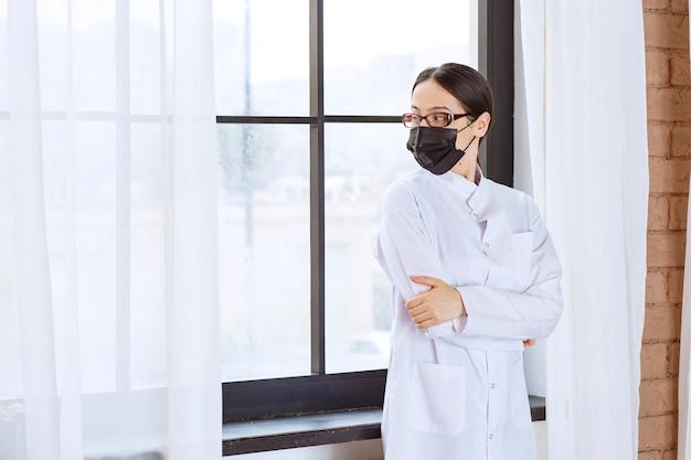 검은 마스크와 안경 창에 서있는 의사.