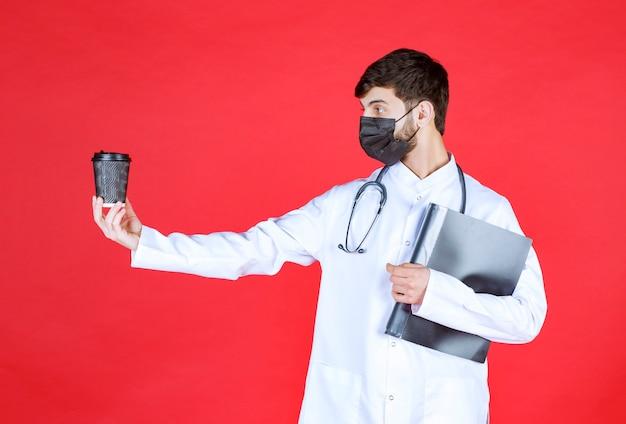 黒いフォルダーと飲み物のカップを保持している黒いマスクの医者。