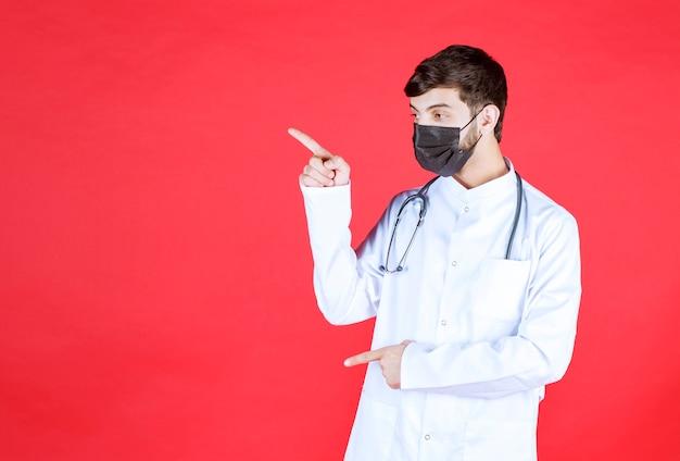 首に聴診器を備えた黒いマスクの医者。