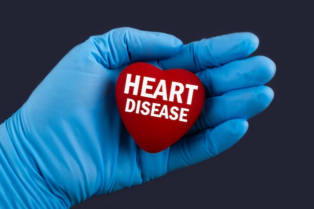 Доктор в синих перчатках держит сердце с текстом болезни сердца, концепции.