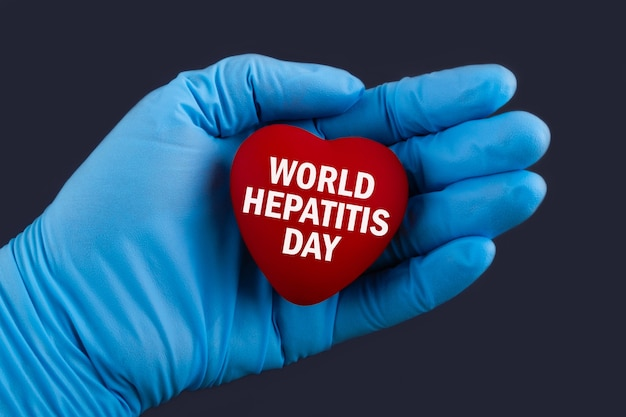 Доктор в синих перчатках держит сердце с текстом всемирный день борьбы с гепатитом, концепция.
