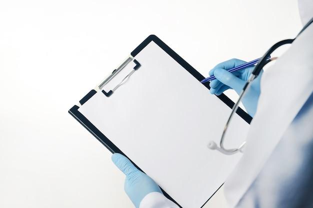 空の空白のシートで医療クリップボードを保持している青いラテックス手袋の医師は白で隔離