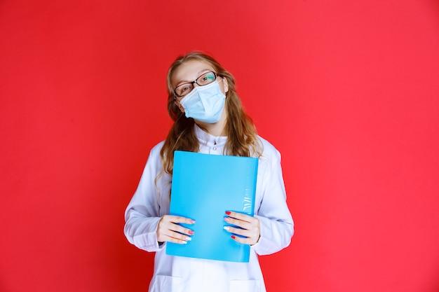 患者の病歴を保持している青いマスクの医者。