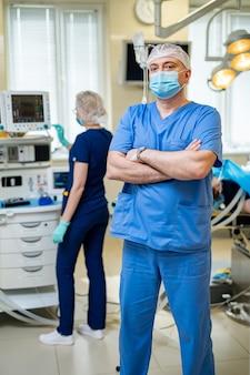 Врач в синей медицинской одежде и маске смотрит на камеру. медицинская палата. первая медицинская помощь. реанимация.