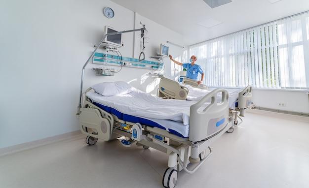Врач в синей медицинской одежде и маске смотрит на экран с параметрами здоровья на нем. медицинская палата. первая медицинская помощь. реанимация.