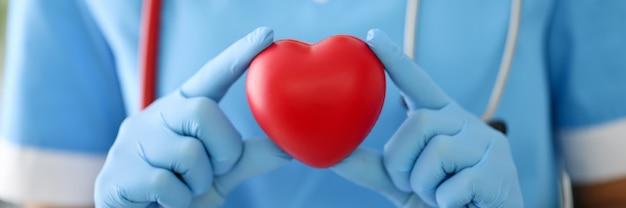 青いスーツ、手袋、赤い聴診器を持った医師はシンボルを保持します。