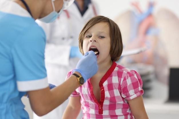 青いスーツを着た医者は木の棒で子供の喉を見ます