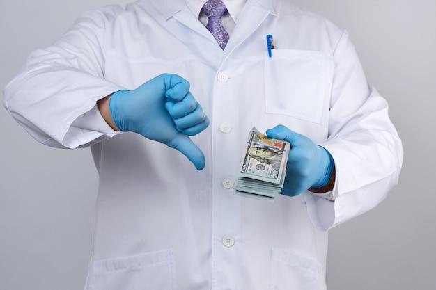 青い制服を着た医者とラテックスの手袋は片手にたくさんのお金をかけ、もう一方の手は悪いジェスチャーを見せています