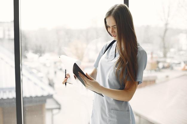 Врач в синей форме. девушка со стетоскопом на шее. женщина с длинными волосами.