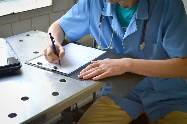 金属のテーブルに座って文書に書く青い制服を着た医者