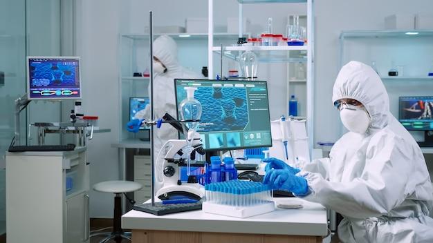 실험실에서 분석 기계를 사용하여 랙에서 혈액 샘플 튜브를 채취하는 작업복을 입은 의사. covid19 바이러스에 대한 치료 연구를 위해 첨단 기술을 사용하여 백신 진화를 조사하는 화학자