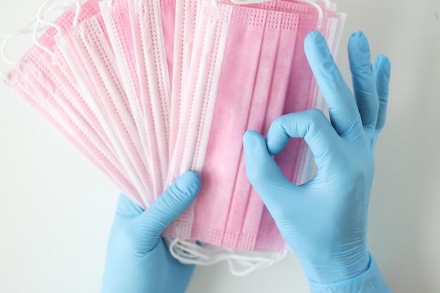 使い捨ての青い手袋をした医師は多くの医療用マスクを持っており、ジェスチャーは優れています。健康安全コンセプトのためのマスクの着用