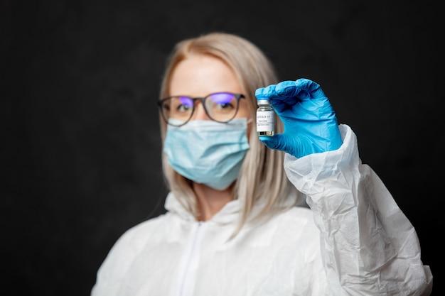 Доктор в маске держит вакцину против covid-19 для вакцинации